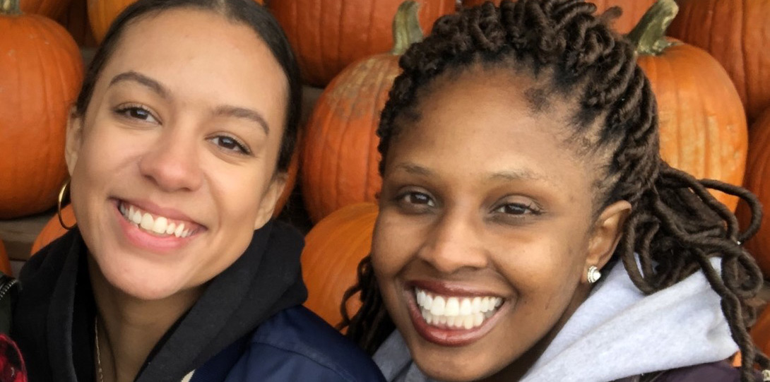 Two PIF Fellows smiling in front of pumpkins