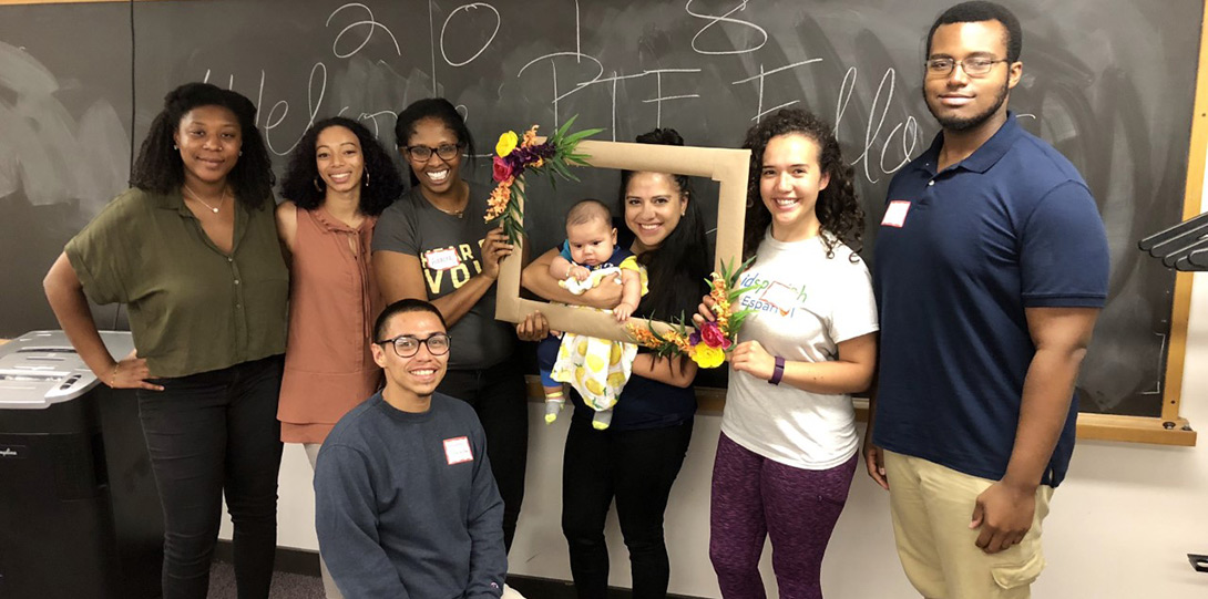 Several PIF Fellows with baby smiling