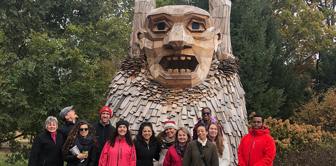 Group of PIF Fellows and mentors smiling in front of troll statue