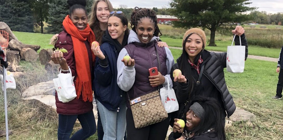 Several PIF Fellows holding apples smiling outside